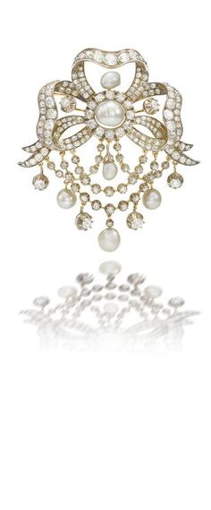 A natural pearl and diamond pendant brooch, circa 1900 Of stylised ribbon design, the central button-shaped pearl surrounded by old brilliant-cut diamonds, highlighted by five pearl drops, suspending swags of similarly cut diamonds, diamonds approximately 16.30 carats total, length 7.5cm