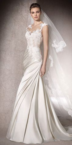Princess wedding dress with a satin skirt draped on one side. A bodice with a sweetheart neckline in tulle with lace, thread embroidery and gemstone appliqués, melts into the skin in a crystal tulle bateau neckline and a plunging back.