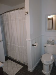 White walls and white wainscoting feel fresh and show off the darker floor and vanity