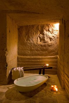 Architecture, Fascinating Bathroom Of Caves Hotel Design Filled With Luxurious White Bathtub And Long Wooden Chair: Hotel Architecture with Prehistoric Caves as Main Building