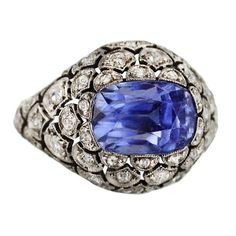 Edwardian 6.00 Carat Sapphire and Diamond Ring set into an openwork scallop-patterned platinum setting accented by circular-cut diamonds weighing approximately 6.00 total carats, the top of the shank featuring a delicate open scroll filigree, made in France.