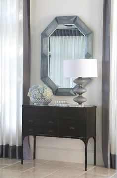 Living room features iron console table with 5 drawers topped with smoky gray glass lamp under octagon mirror flanked by windows dressed in white curtains with platinum gray trim. Console Table Living Room, Living Room Sets, Living Room Bedroom, Living Room Interior, Living Room Furniture, Modern Console Tables, Transitional Living Rooms, Wrought Iron Console Table