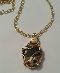 Small (15×20mm) tigers eye pendant wrapped in 14KGF with sterling silver accents.