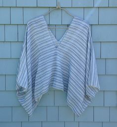 Blue, Gray and White Striped V-neck Top ($68)  * Medium/ Large * Oversized but lightweight * Unlined * Zigzag stitch detail throughout  * Brown suede emblem at lower center back * Made of locally sourced cotton * Handcrafted in Maine * Dry clean or hand-wash in cold water and line dry * Our garments are eco-friendly and will not last forever so Mother Nature can