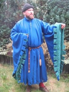 A houppelande, from around 1400, belted low at the waist. With long funnel shaped sleeves and dagging at the edge of the sleeves, typically in a contrasting colour