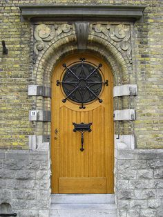 Gorgeous curved wooden door with star-shaped iron grating over a circular window