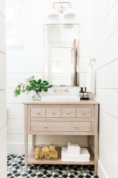 Charming powder room features a bleached bath vanity placed on black and gray mosaic floor tiles and fitted with a shelf, drawers donning small polished nickel knobs, and a Classically Redefined Rectangular Semi-Recessed Vitreous China Lavatory Sink positioned beneath a polished nickel faucet mounted to a white shiplap wall under a beveled medicine cabinet lit by a white vintage downlight sconce.