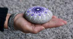Beschilderde meditatie steen met onder andere paarse tinten. Circa 9 cm diameter om een indruk van de grootte te geven. De beschilderde steen is 466 gram. De mandala steen is afgewerkt met een laagje vernis maar kan alsnog niet gebruikt worden voor buiten, etc. Elke steen is uniek en uiteraard handgemaakt. Op de achterkant van de beschilderde steen staat mijn naam. De stenen komen uit Duitsland en Frankrijk. Voor het idee ben ik geïnspireerd door Elspeth McLean. De stenen zijn verpakt in…