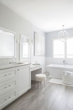 Feiss Oberlin Satin Nickel Pendant Light hangs over a freestanding rectangular bathtub placed under windows framed by gray upper walls and white tiled lower walls.