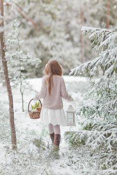 An enchanting little girl carries a basket in one hand, a lantern in the other on her walk through the woods where the evergreens are frosted with snow.