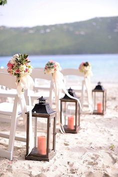 How To Plan A Destination Wedding, Beach wedding with candles and bouquets on white chairs.