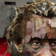 """Massive Optical Illusion Made of Recycled Objects - """"The massive portrait of Malian actor Sotigui Kouyaté is the latest work of French artist Bernard Pras. It was created entirely out of recycled materials such as clothes and rags, wood, glass lanterns, dishes, rubber and other trash Bernard would gather from the installation site."""""""
