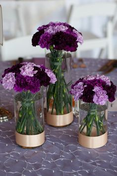 Trio of cylinder vases with varying shades of purple carnations mounded on top and  simple champagne ribbon sash at base of each vase.