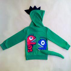 Sudadera de dinosaurio para niños. Sudadera en color verde con capucha. Estampación de #dinosaurios delante y a la espalda. Detalle en fieltro negro de cresta de dinosaurio en la capucha y detalle de rabo de quita y pon con imperdible. Es una sudadera muy original y divertida que encantará a los renacuaj@s de la casa! #ropaoriginalniños