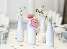glass bottles painted white filled with pretty florals via http://www.abeachcottage.com/2011/06/bc-saturday-club-your-questions-pale-blue-table-dressing.html #florals #flower #centerpiece