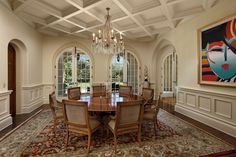 Gorgeous natural light floods into this glorious formal dining room boasting ached french doors. A large colorful piece of art hangs on the wall adding a bright and contemporary touch.