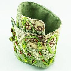 He encontrado este interesante anuncio de Etsy en https://www.etsy.com/es/listing/126043422/fabric-cuff-bracelet-green-art-jewelry