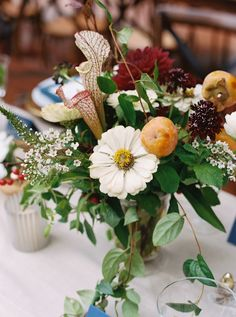white green and red florals; pineapple productions; table floral arrangements featuring fruit;