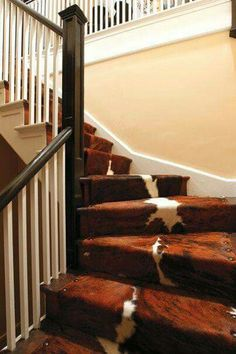 Cow hide on the stairs what a great idea to give it the western touch.