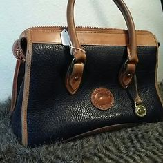 """Navy blue Dooney  & Bourke All Weather Leather bag Good used condition D & B satchel.  100% leather.  Interior has 3 pockets.  Does have some general wear marks and one corner is worn.  Shows some wear on edges of leather handles.  11"""" w x 8"""" h with a 3"""" drop.  Overall good condition. Dooney & Bourke Bags Satchels"""