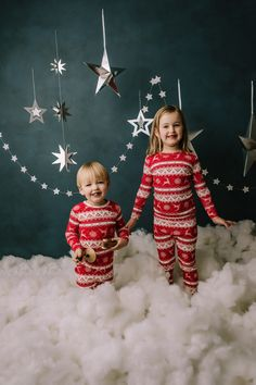 holiday mini session photo shoot christmas pajamas siblings silver hanging stars blue backdrop puffy cotton clouds reindeer
