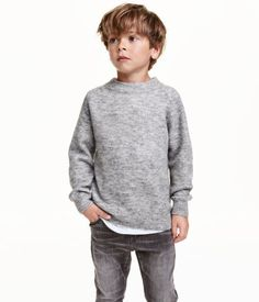 Gray melange. Sweater in a soft knit with wool content. Small stand-up collar, long raglan sleeves, and ribbing at cuffs and hem.