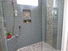 Example sea glass subway tiles for shower walls (would not use pebbles as accent though). Perhaps a less contrasting grout color? Ocean Glass Subway Tile Shower Featuring Pebble Tile