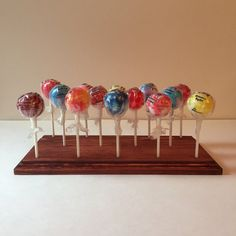 Presenting D & Js Custom Lollipop and Cake Pop display stands. Check out my other items for more cake pop display ideas! Perfect for holding lollipops or cake pops to display on a table, to cool down while baking, take to parties, give as gifts, you name it! Features: * Holds 14 Cake Pops or lollipops * Durable and sturdy wood construction * Attractive routered edges * Dark Mahogany stained Options: * 5/32 Hole size: fits all standard sized sticks * Larger hole sizes available...