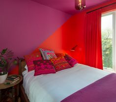 Don't be afraid to try unexpected color combos. This bedroom shows how well magenta and red can look together. For a truly daring space, experiment with different palettes — but be sure to test your combinations with oversize paint samples before going all in.