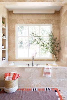 Warm up cold tiles with a house plant or leafy arrangement like this relaxing retreat. If you're lacking a green thumb, choose wet-loving vegetation such as a Boston fern or dracaena.  Shop a similar look:basket, $68,serenaandlily.com