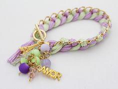 Pulsera tejida: de hilo artesanal en color lila con verde menta, con accesorios dorados en bisutería.
