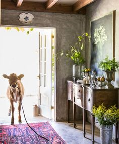 Upon purchasing the property in 1992, Kurt's first order of business was to relocate the entire cabin so it didn't rest right on the property line. An antique mahogany sideboard serves as a bar in this entryway. To its left, Haley the dairy cow wanders in for happy hour.