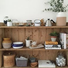 simple shelf styling... stacked enamel plates, cookery books, baskets and jars