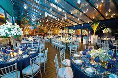 Inspire-se na clássica e moderna decoração de Daniel Cruz. Com os tons de azul presentes nas taças e toalhas. Cadeiras e flores brancas deram ainda mais charme ao décor.