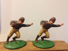A PAIR OF CIRCA 1920's, HUBLEY MANUFACTURED (LANCASTER, PA. ), SOLID AND HEAVY ANTIQUE CAST IRON WITH FANTASTIC COLORFUL POLYCHROME PAINT, NOSTALGIC FOOTBALL PLAYER WITH FOOTBALL ART STATUE BOOKENDS,
