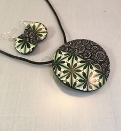 By Debby Wakley Pendant and earrings made using Kato poly clay. Following Cara Jane Hayman kimono cane. The green cane was made by Marie Leckie