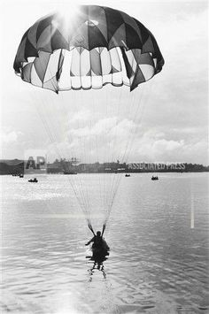 A nurse lands in the Saigon River during a recent maneuver in Vietnam on Dec. 28, 1964. The parachuting nurses, a new corps which is flown into battle areas and dropped to attend to the wounded, is one of the most recent uses of women in the government?s struggle against the Viet Cong. (AP Photo/Horst Faas)  ID: 6412280130