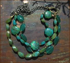 Three Layer Asymmetric Multi Gem Green/Blue Necklace Amazing colors on this necklace, blue green beauty! Translucent Green Onyx (all hand wired), angular Chrysocolla and varying sizes of Grade AAA Magnesite twists mix with assorted Brass beads. All are suspended by dual Brass-clad chains and a ginormous Brass-clad lobster clasp. A really nice piece.