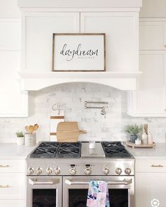 White kitchen with GE Monogram range and pretty white hood, marble subway tile backsplash, and pretty wood styling details #kitchendecor #kitchendesign #kitchenbacksplash