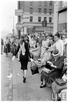 Vikki Dougan, the inspiration behind Jessica Rabbit, walks down a 1950s street