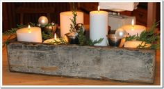 chippy old seed box for holidays / table centerpiece / white candles / cut evergreen / pinecones and Christmas ornaments