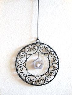 Kolečko s perleťovou květinkou - šedé Kolečkoje vyrobeno z černého žíhaného drátu, kteřý je dozdoben skleněnými korálky a perleťovou květinou. Průměr kolečkaje cca 8cm. Lze jej zavěsit kamkoliv... Je ošetřen proti korozi, ale ve vyšší vlhkostí může chytit patinu. Cena za kus.