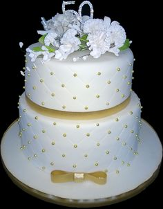 """Golden Wedding Cake – This 50th wedding anniversary cake was a dream to make. A 10"""" and 8"""" decadent chocolate cake with a creamy vanilla buttercream filling. Quilting pattern around each cake with golden balls and the flowers are based off the bride's bouquet from 50 years ago. Finished with a diamante 50 and golden ribbon and bow."""
