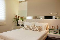 """O quarto, de 14 m², foi decorado pela designer de interiores Marília Gabriela Dias. Os moradores queriam um ambiente """"clean"""" para relaxar. O destaque do quarto é a cabeceira, composta por um painel de MDF laqueado e com iluminação embutida."""