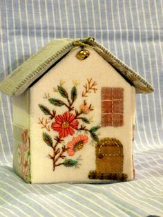 LOVE this little embroidered house with pockets on the sides to hold a package of needles and a rooftop which opens to store skeins of threads!