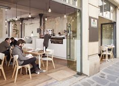 Low-energy hanging Plumen bulbs, stripped away wallpaper, and flowering plants growing out of stainless steel tins make this a no-fuss, super cool coffee laboratory.     [Cafe Coutume, Paris]