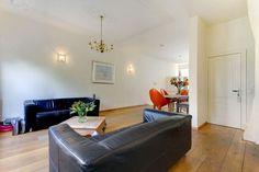 Ruime woonkamer met ornamenten plafond en toegang naar de tuin. Vanuit de woonkamer is het toilet bereikbaar en de trap naar de eerste verdieping.