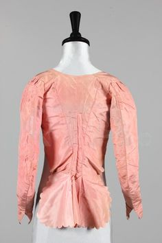 "Bodice, circa 1780. Kerry Taylor Auctions, lot 190. Item Description: A pale pink silk ""caraco"" bodice, circa 1780, with high-cut front closure flaps, low boned back with pinked, scalloped tails, curved sleeves, lined in linen."
