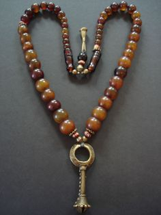 by Luda Hunter | 'Kirdi Bronze'.  A long graduated strand of African amber beads with gorgeous rich colouring and patina from Mali, old African handmade oval brass & flower beads and striped bone beads with an old African Kirdi bronze dance pendant | Sold