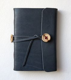 A small leather journal made with various papers from Huldra Press